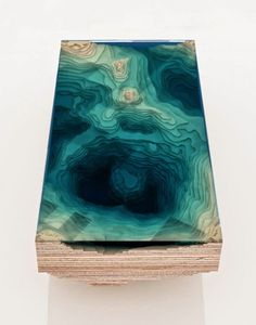 Abyss Table by Duffy London A coffee table using layers of sculpted glass, Perspex and wood, arranged like a 3D representation of a geological map of the ocean.
