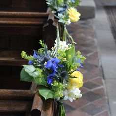 Cute pew ends with yellow roses, blue delphinium, Veronica, daisies and freesia www.mrs-umbels.co.uk