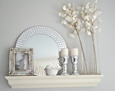 I love this shelf display, the light tones, the shingled mirror, and the shiny candle holders!!