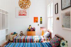 Quarto infantil tem camas patente e colchas coloridas.