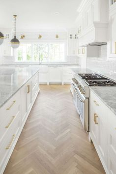 White classic kitchen with Midcentury modern island pendants and herringbone wood floor. White English farmhouse style home by The Fox Group. Come be inspired these English Farmhouse Style Decorating Ideas. #modernfarmhouse #englishfarmhouse #interiordesignideas #farmhousestyle #decoratingideas #kitchendesign #whiteoak #herringbone #woodfloor