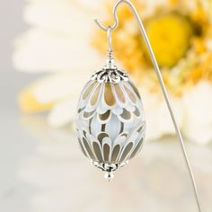 "Delicate petals of olive and light blue petals encased in clear glass. This is similar to the Lotus Flower beads except it is a more complicated pattern of petals repeated top and bottom over the central striped pattern. A larger size in a teardrop shape pendant with smooth surface measuring 1-1/4 "" long by 7/8"" around at its widest."