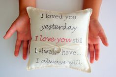 Ring bearer pillow with a quote printed on it.