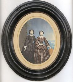 Large hand-colored salt print of two women with very thin waists posed arm-in-arm in front of an elaborate painted-in background. German ca. 1860