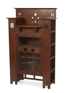 LIBERTY & CO., LONDON ARTS & CRAFTS OAK SIDE CABINET, CIRCA 1910 with pierced upstand and stepped top above an open shelf and single glazed door, the pierced sides with glass backed cut-out plant motifs, enclosing bookshelves 85cm wide, 139cm high, 38cm deep