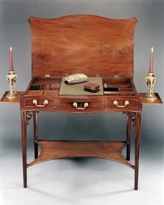 A George III Chippendale Period Dressing Table. Circa: 1770. An exceptionally rare Chippendale period dressing table. The table having a lift up top revealing a fully fitted interior, complete with all original compartments, brushes and toilet mirror, above a serpentine front with three dummy drawers and original chased handles.  The table supported on four moulded legs headed by pierced angle brackets and united by a platform stretcher. To each side of the table is a candle slide.