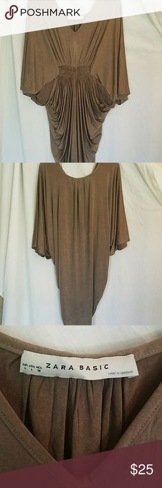 """Zara Basic Tunic Mini Dress Gathered Waist Shirred Zara Basic, tunic/ mini dress. Butterfly Dolman Type Sleeves, gathered at waist. 92% acetate 8% elastane. This piece is slinky and swingy, kind of a light mocha brown with some shine to it. A hi-lo design, 33"""" long in back top to bottom and 25"""" from v neck to bottom in front. 3/4 sleeves. 32"""" across front bust sleeve to sleeve laid flat. I tried to model it to show more of its design, its really a beautiful piece.  I don't do trades, thanks…"""