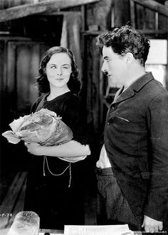 """Charlie Chaplin and Paulette Goddard in Modern Times (1936) "" Charlie casts a disapproving eye, though he himself was stealing food not that long before."