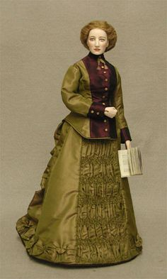 """""""Victoria"""" is based on a portrait of Victoria Woodhull, who ran for President of the United States in the 1870's. She published and edited a newspaper and was a stock broker on Wall Street, quite extraordinary for a woman of her time.  Under Victoria's 1870's style two piece silk dress is a petticoat, a chemise, drawers, corset, and a bustle. She wears patterned stockings and laced boots."""