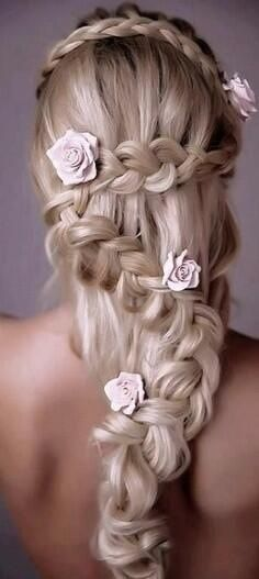 Original semi-recogido para novia con trenza y rosas como complemento.