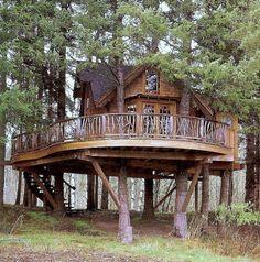 Casa de madera de dos plantas sostenida en los árboles con extensa terraza