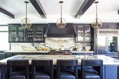 Contemporary kitchen boasts three Arteriors Caviar 1 Light Pendants illuminating a black stained ...