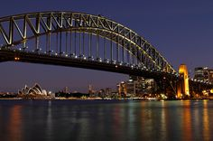 Harbour Lights Twilight view of Sydney Harbour Bridge, Sydney Opera House and Circular Quay. This photograph was taken at Milsons Point just outside the entrance to Luna Park.   It's about 20 minutes after sunset and the eastern sky is fading from lavender to a deep navy blue. A long exposure smooths out the water and allows the patterns and shadows created by the bridge lighting to be seen in the reflections on the harbour surface.