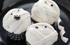 """fondant mummy cupcakes:  Unwrap a sweet secret: mummy cupcakes are an easy treat. Frost cupcakes with a smooth layer of white icing. Roll fondant thin (1/8""""), and cut long strips, 1/3"""" wide. Lay strips in several directions atop cupcakes to create a mummy wrap; be sure to leave space for sugar or fondant eyes, and other decorations."""