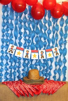 Create your own Cowboy Party backdrop by hanging some blue streamers and red balloons on the wall!