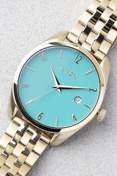 """With a sleek design that brings a stylish impact, the Nixon Bullet Light Gold and Turquoise Watch knows how to impress! A classic design features a turquoise watch face with light gold time markers and hands, surrounded by a matching 1.5"""" setting. Watch has a 6"""" circumference (closed), plus 1"""" of extra links included. Water resistant up to 50 meters."""