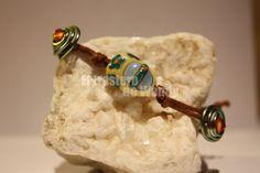 Pulsera realizada en hilo de cuero marrón, motivos en alambre de color verde con abalorio naranja y entrepieza central  de zapatito de porcelana.