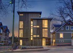 Das Exterieur-Design des Hauses mit der Ansicht in der Nacht mit Lampen brighting Glasfenster und auch Holzaußenwand
