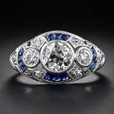 This supreme Art Deco dream ring, hand crafted in platinum - circa 1925 - centers on a sparkling 1.05 carat European-cut diamond, closely guarded by a pair of neighboring diamonds. The three main sparklers are each bezel-set and float atop a gracefully curved 'cigar band' style ring accented with rich royal blue calibre sapphires on all four sides. Artfully hand pierced diamond-set shoulders lead to a hand engraved ring shank.