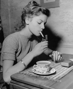 Lauren Bacall haveing a coffee & a smoke. So young!