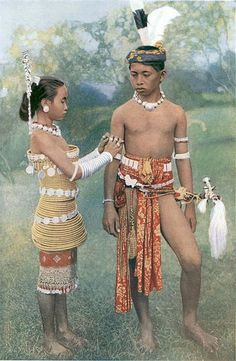 Dayak Tribe | Borneo-Indonesia. Young Iban boy in traditional clothing. Certainly look very fine in gala dress; though the boys may not wear as much as their sisters, their silver ornaments, scarlet waist-cloths, elaborately ornamented swords turbans, make them fit companions for the girls. The boys' costume is more comfortable than the girls', but ornament in dress is a passion of the Sea Dayaks, small child, left, with his plumed hat necklace, is already a martyr to fashion.