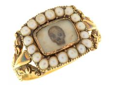 FINE ART SALE 18/09/19- Lot 13 AN ENGLISH GOLD MOURNING RING, 1831 the oblong tablet inset with a painted miniature of a human skull in split pearl surround, on fluted and chased gold hoop, pierced shoulders, the underside engraved Hester Grazebrook Ob 27 June 1831 At 78, 3.6g, size N½ Estimate: £700 - 900