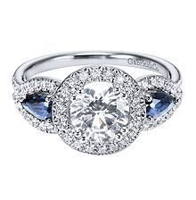 Dramatic Gabriel & Co Diamond Engagement Ring featuring a Round Center Diamond Halo and Pear Shaped Sapphire Side Stones.