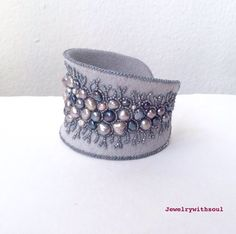 Your most favorite design is back :)  68 pearls! This delicate bracelet is stitched on light grey felt, I used freshwater pearls of different tones of greys - silver, gunmetal, silver peacock blues and greens, creams mauve so and whites as well. Some are big, some are the tiniest, some are smooth, some are rustic. They are embraced by tiny silver lined light grey rainbow seed beads.  Bracelet is neatly backed with light grey ultrasuede. The bracelet is adjustable and has nice unusual…