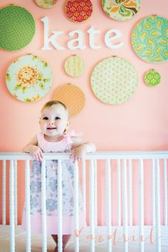 Aedriel's Inspiration for the Everyday: DIY Nursery Wall with fabric covered rings- some burlap with ribbon bow accent, some damask/Moroccan pattern, some solid pink.