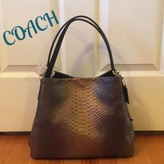 "NWT Coach Phoebe Leather Shoulder Bag This bag is STUNNING!!!  Coach Phoebe Snake Embossed Leather Shoulder Bag w/ Sparkle. Pics don't do justice!!!  Metallic gold with gold tone hardware, dual shoulder straps w/8.5"" drop, 3 open compartments, 1 in middle has zip closure, snap closure bag, leather hang tag.  Black sateen fabric with full length zip pocket, 2 slip pockets. Care card included. Measures approx 13""X11""x6. New Coach Design. Awesome smell of leather  Coach Bags Shoulder Bags"