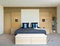 Modern bedroom with a walk-in closet and a wooden accent wall