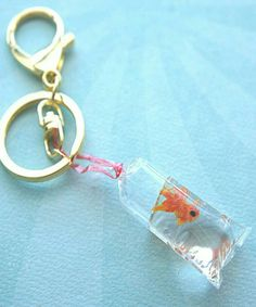 This keychain features a goldfish in a bag charm. The tiny goldfish is made from polymer clay and the water is made from resin material. the charm measures cm in length and is tied with a red string that hangs from the gold tone key ring. Resin Crafts, Fun Crafts, Diy And Crafts, Tape Crafts, Creative Crafts, Upcycled Crafts, Homemade Crafts, Preschool Crafts, Bottle Charms