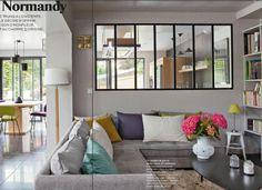 canapé gris, coussins colorés, vitre type industriel entre cuisine et salon Source : Journal de la maison