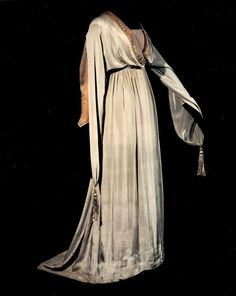 Liberty afternoon dress of pale blue-grey crepe with draped crossover bodice, medieval revival sleeves, and semi-full trained skirt; embellished with ivory chiffon trim and Chinese embroidery; British, c. 1910