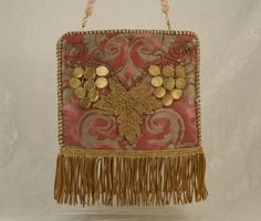 New handbag from 1920's French handmade applique of grapes and grape leaves mounted on vintage pink and metallic gold Fortuny fabric. 19th c. French gold coil fringe and antique cording. Hidden magnetic closure secured by vintage button. Silk lining. Removable handle of faceted pink Chalcedony, pink freshwater pearls and gold vermeil can be worn as a necklace. Fun with jeans or dress-up.
