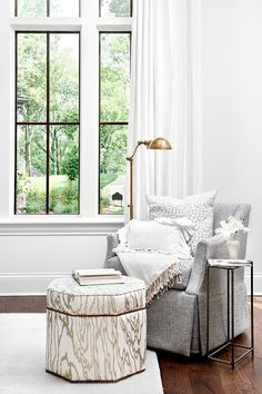 A gray skirted chair topped with a gray pillows and cream throw blanket complementing a white and gold faux bois stool placed on a white rug.
