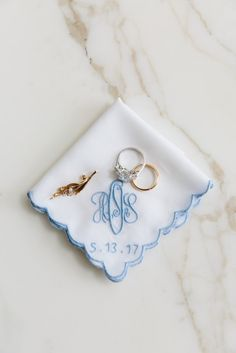 "My bridesmaids gave me this beautiful monogrammed handkerchief with my new initials and wedding date at my bridal shower, as a ""something blue."" Resting on it are my rings, and a gold and diamond pin from my maternal great-grandmother. My grandmother gave it to me on my 25th birthday, the day after Ben and I got engaged, and I wore it on my veil. - Over the Moon"