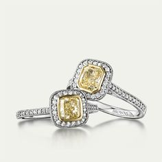 Natural Fancy Yellow Diamonds with a halo of brilliant diamonds set in 18ct Gold