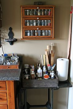 To the right of the cubby is an old typewriter stand holding a German beer crate full of paints, glues and other supplies.