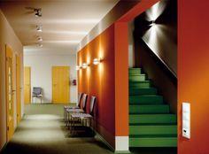 Parede laranja e escada verde.