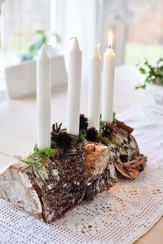 Tronco con 4 velas blancas sobre un camino de mesa a crochet blanco.