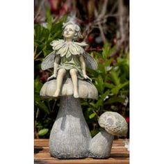 Curious fairy looks upward as she sits perched on a mushroom  and w...