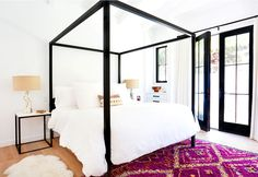 White walls, black bed frame, white bedding, printed pink rug, and faux fur white rug