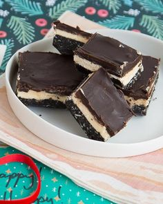 Nanaimo bars originated in British Colombia. Decadent layers of chocolatey almond and coconut flecked crust, rich custard filling, and topped with a hard chocolate shell.