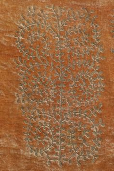 A Mariano Fortuny stencilled peach velvet jacket, 1920-30. with circular label 'Mariano Fortuny Venise', delicately stencilled with gold fern-like scrolls, lined in peach silk, two brown and white Murano glass beads to neckline cords