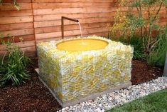 Replace gabion stones with recycled glass. Yellow and white glass pieces create a stunning base for this fountain.