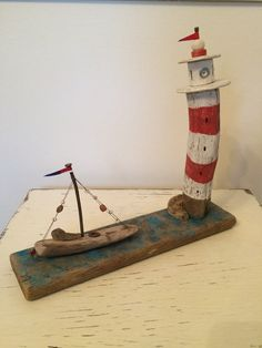Driftwood Lighthouse 23cm Tall x 25cm Wide x 6cm Deep with small boat on base. White and red striped driftwood with white top. blue base and small masted boat on base. A delightful ornament. This is not a toy.