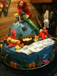 A birthday cake with a real Arial the little Mermaid, and she is joined by her friends