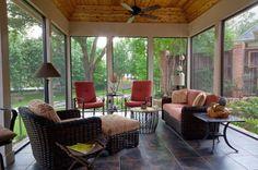 Veranda chiusa con divano in vimini e poltroncine