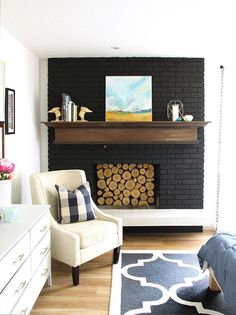 Such a cozy spot! Black paint was perfect for this old outdated fireplace makeover. This painted black brick fireplace is so good and I love the wood slice insert! A total update to the old red brick. Black Brick Fireplace, Painted Brick Fireplaces, Paint Fireplace, Old Fireplace, Fireplace Design, Fireplace Ideas, Fireplace Decorations, Fireplace Pictures, Craftsman Fireplace